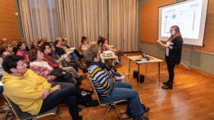 Lehrer sitzen in einem Raum und hören sich eine Präsentation an