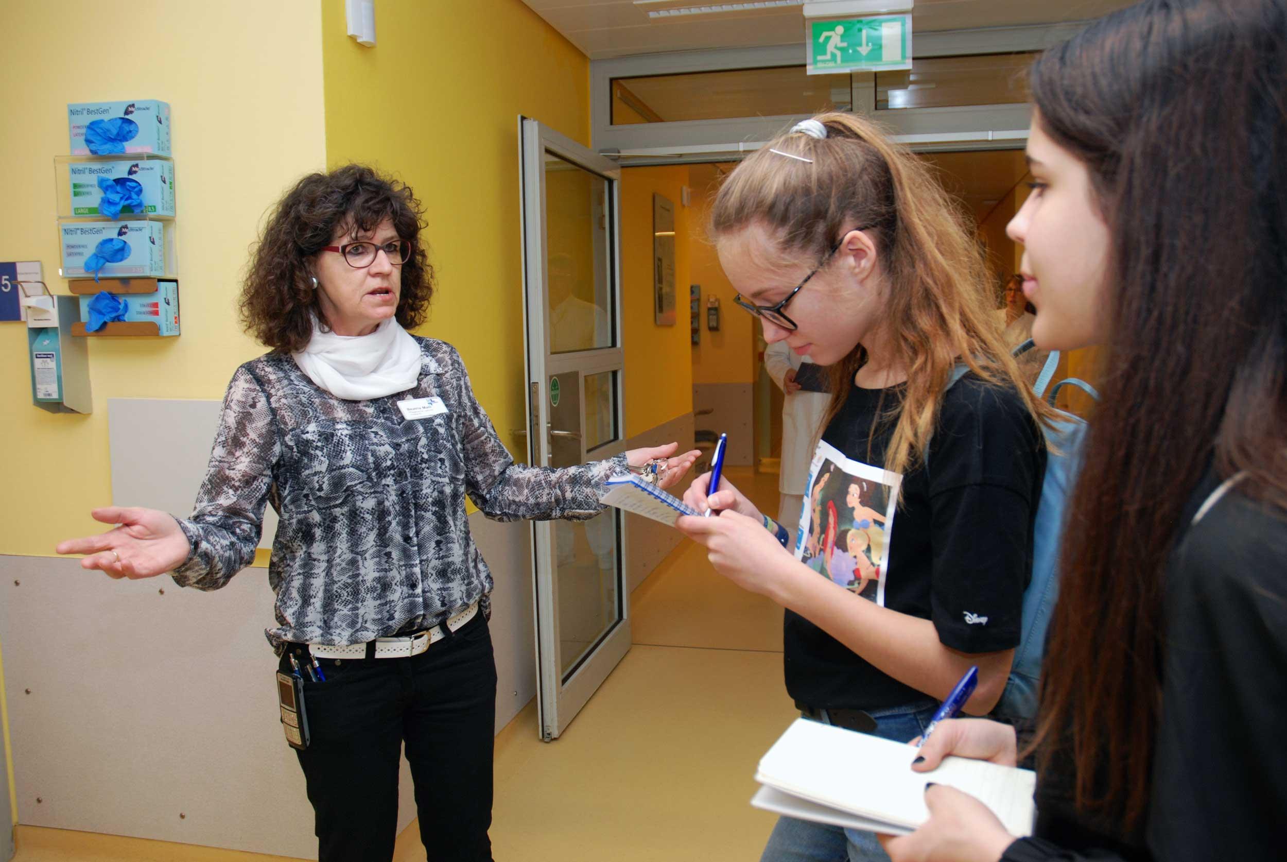 Eine Pflegerin erklärt zwei Schülerinnen etwas, die mitschreiben.