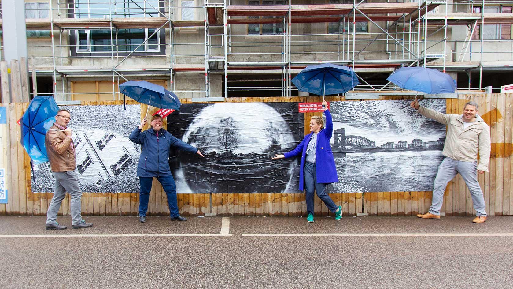 Mitarbeiter der WBG mit Regenschirmen vor den SchmaZ-Siegerfotos